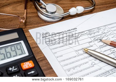 Health Insurance Claim Form With Stethoscope On Clipboard, Syringe, Calculator And Pen