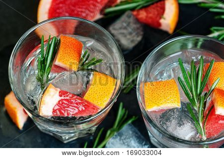 Top view of cocktail with grapefruit ice and rosemary dark stone background selective focus