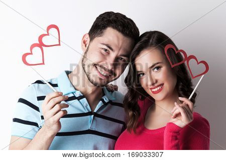 Happy smiling couple celebrating Valentine day with funny party heart shaped glasses on stick