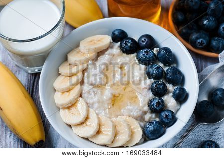 Close up of oatmeal with banana and blackberries in white bowl on wooden background selective focus. Healthy food concept.