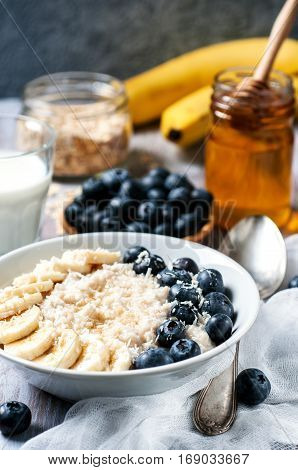 Oatmeal with blackberries and banana on wooden background selective focus vertical. Healthy food concept.