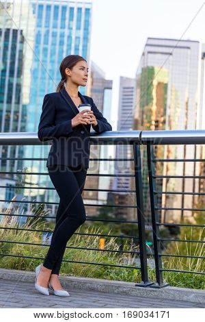 Businesswoman drinking coffee on break in business city center outside office buildings background.