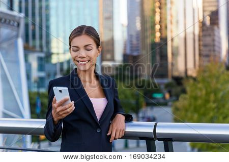 Woman sms texting using app on smart phone in city business district. Young business woman using smartphone smiling happy wearing suit jacket outdoors. Urban female professional in her 20s.