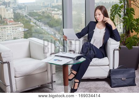 Young Asian Business Woman In Suit Looking At The Chart On The Sheet