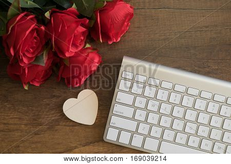 Wooden heart near a keyboard with red rose on office table happy birthday romance congratulate concept.