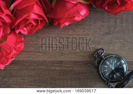 vintage pocket o'clock on wooden table with artificial red roses with copy space