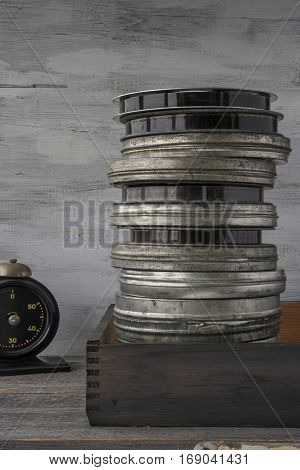 A stack of old movies in a wooden box and a timer are on the table