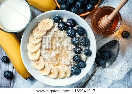 Top view of oatmeal with blackberries and banana on wooden background selective focus. Healthy food concept.