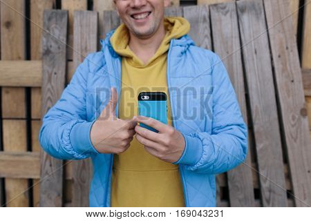 young man in a blue jacket holding a mobile phone in one hand and the other showing a thumbs up on wooden background