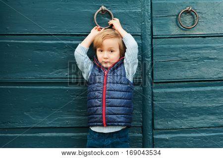 Outdoor portrait of a cute little boy wearing blue waistcoat, standing next to blue wooden door