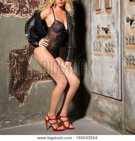 Slim Blonde Girl Posing In Black Lingerie, Leather Jacket And Red High Heels Near The Electrical Pan