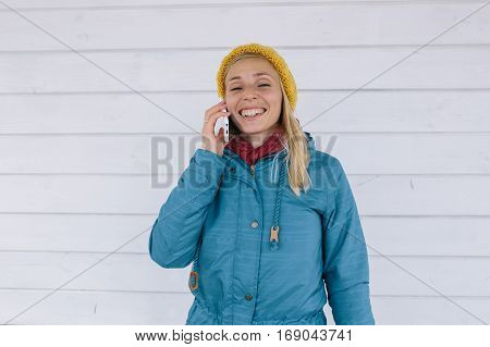 smiling young woman talking on the phone. woman in yellow knitted hat and a blue jacket using smart phone on white wooden background