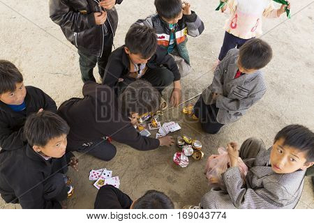 Ha Giang, Vietnam - Feb 7, 2014: Unidentified group of Hmong children playing cards in an old market