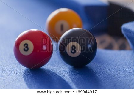 Red, yellow and black billiard balls in a pool table. Focus on red and black billiard balls