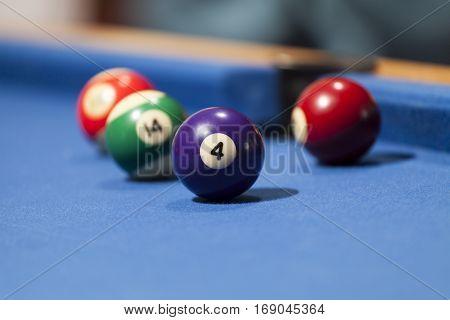 Purple, green and red billiard balls in a pool table. Focus on purple billiard ball