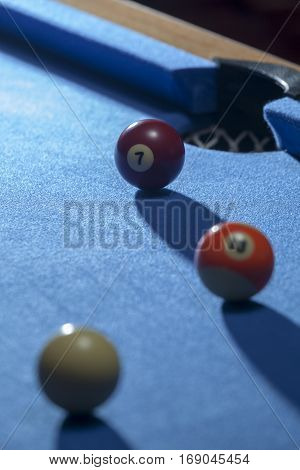White, orange and red billiard balls in a pool table. Focus on red billiard ball