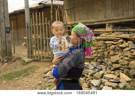 Yen Bai, Vietnam - Apr 12, 2014: Portrait of unidentified Hmong mother and son playing in front of their home