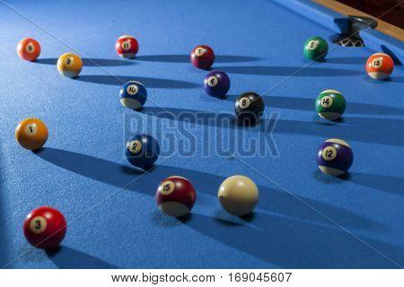 Billiard balls in a pool table. Focus on black billiard ball