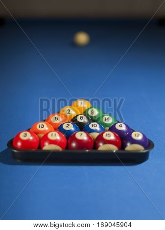 Pool billiard balls in a plastic rack - commonly used starting position. Focus on black billiard ball
