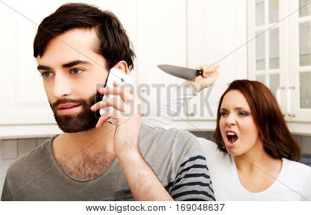Angry young woman hitting men with frying pan.