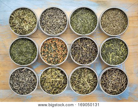 green tea sampler - top view of loose leaf teas in metal cans against grunge wood poster