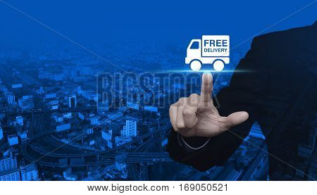 Businessman pressing free delivery truck icon over modern city tower street and expressway Business transportation concept