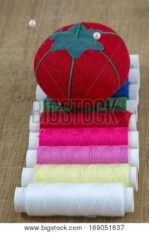 Red pincushion with two pins are on the colourful threads on the light wooden background