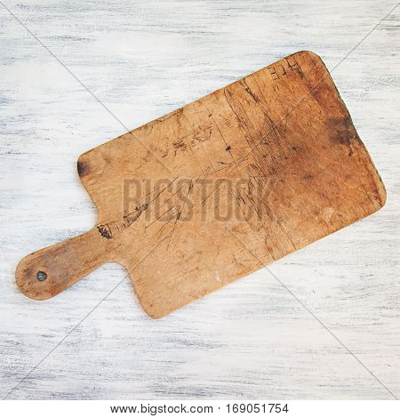 Old scratched kitchen cutting accessory on wooden background