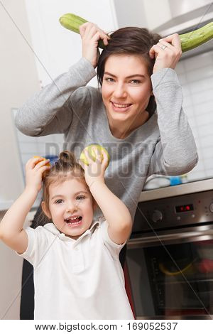 Brunette and daughter with fruit and vegetables in joke kitchen