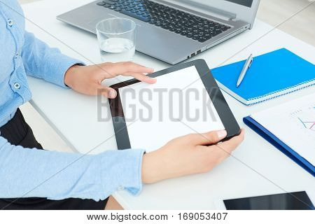 Female hands holding tablet in office background.