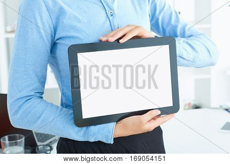 Young famale secretary holding tablet in hands sitting at office. Tablet with empty space for advertising.
