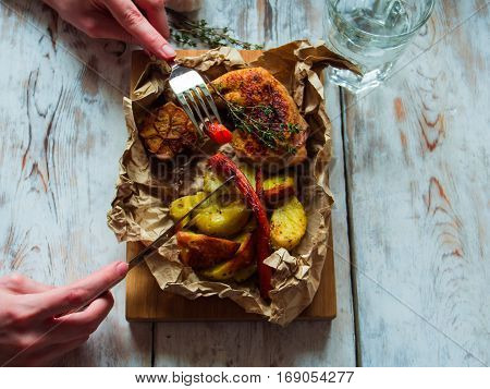 Top view woman hands eating chicken legs grilled on a wooden board with vegetables. Dinning concept.