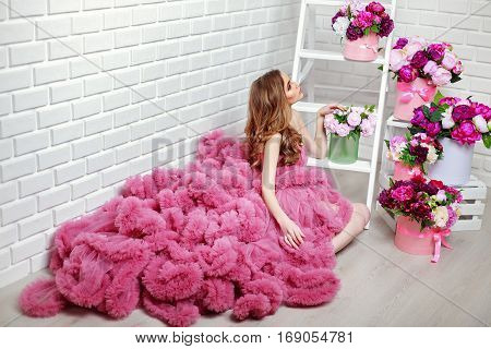 Horizontal portrait of young female wearing uncommon pink dress sitting near flower bunches.