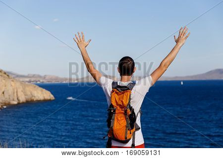 Young guy with hands up on hill in sea background