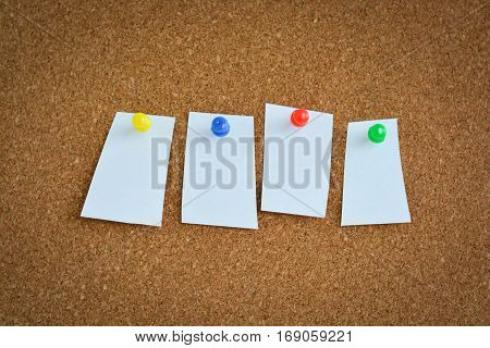 Blank memo notes on cork billboard and pins