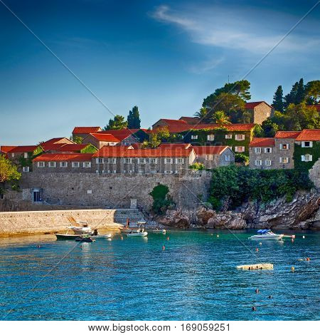 Adriatic sea and medieval houses on famous island-hotel Sveti Stefan, Montenegro in afternoon sunlight. Square toned image