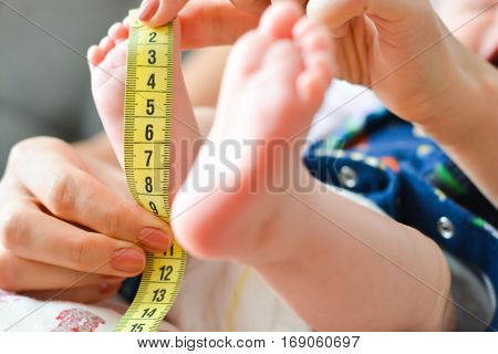 Mother measuring tiny baby foot with a meter