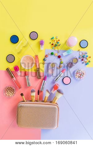 Make up products with golden pursue pop art top view flat lay scene