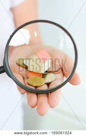 Toy house under magnifying glass in woman hand suggesting house search