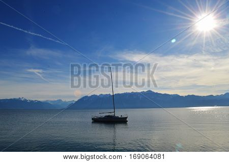 Boat on the lake amid the Alps on a Sunny day with the glare of the sun.