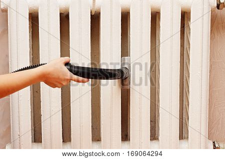Woman vacuuming thoroughly cleans the radiator heating.
