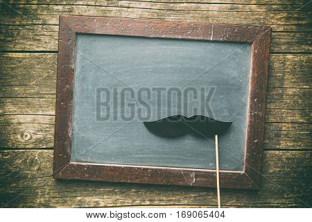 Blank chalkboard and fake mustache. Top view.