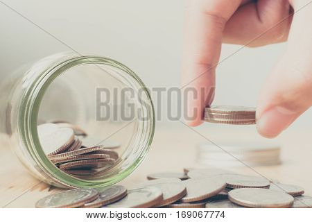 Concept saving money business finance for investment Coins in glass and hand putting money