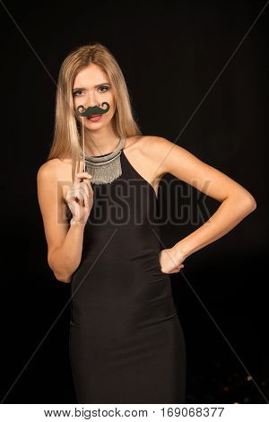 Gorgeous blonde woman posing with fake mustache on stick