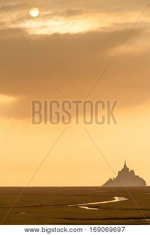 Silhouette of famous Mont Saint Michel on Normandy coast at sunset, France