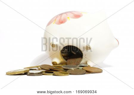 Overloaded piggy bank and coins isolated on white.