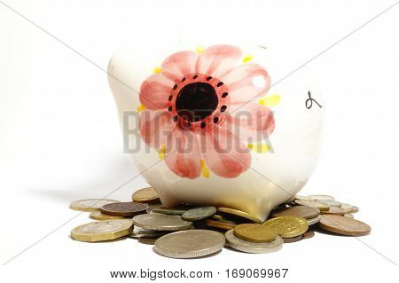 Piggy bank and coins isolated on white.