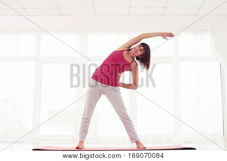 Low angle of excited woman standing side stretch in the gym. Open position and inducing feelings of calm. Standing supported side stretch