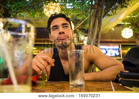 Cheerful man grimacing in the bar. Horizontal indoors shot.