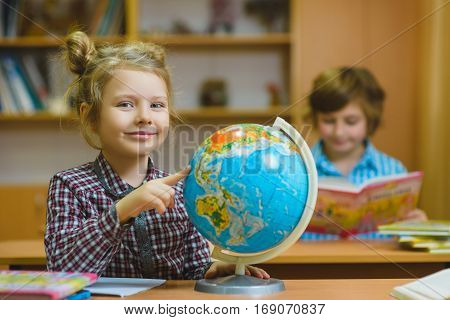 smiling girl showing on globe at school classroom. Educational and school concept.